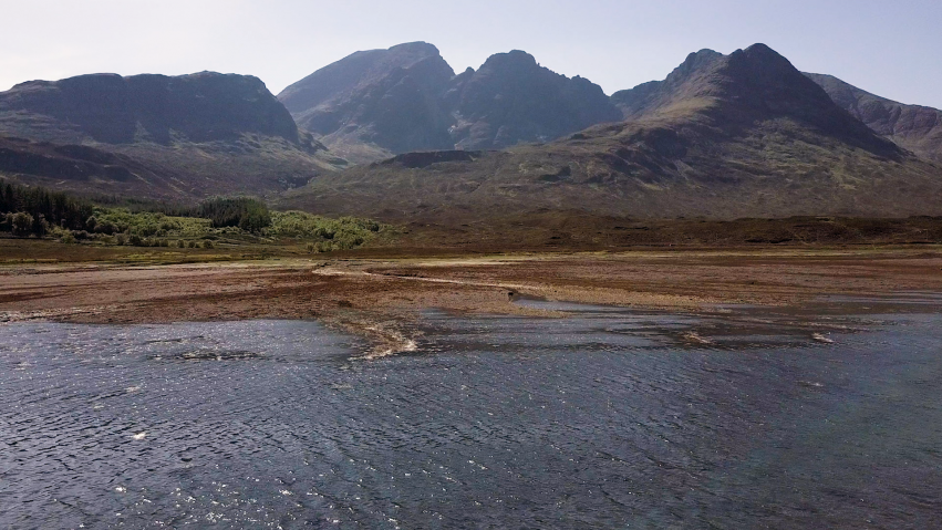We see an aerial shot showing mountains above the water.