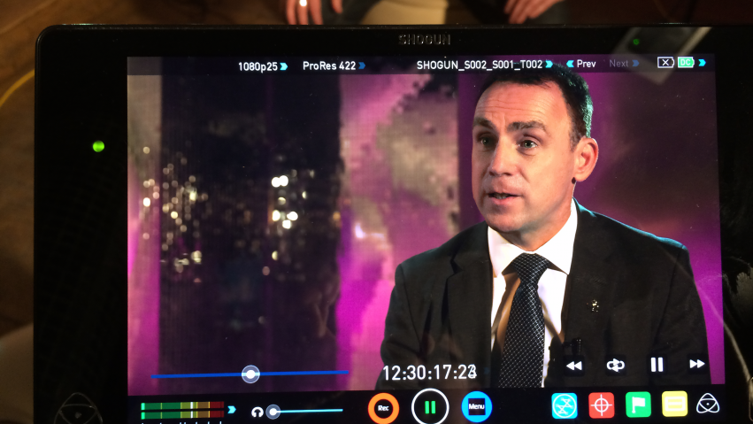A monitor show a shoot of a business man being interviewed in front of a pink background.