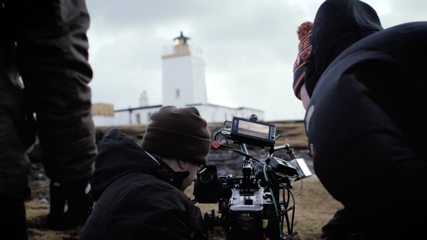 Three people crouch around a camera as they film a lighthouse in the distance.