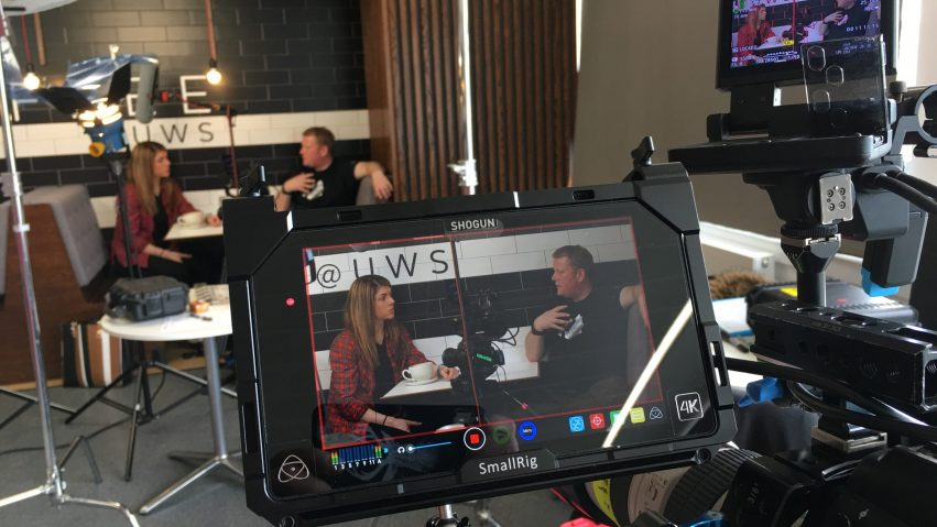 A camera and monitor show two people, a man and a woman, sitting at a cafe table talking.