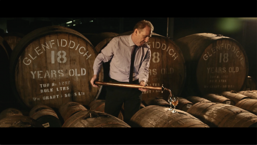 A man stands in front of large whisky casks as he pours a sample into two nosing glasses