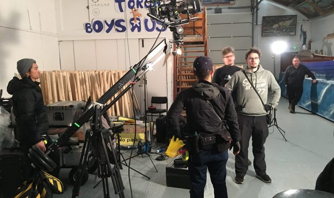 Crew stand around a camera on a jib.