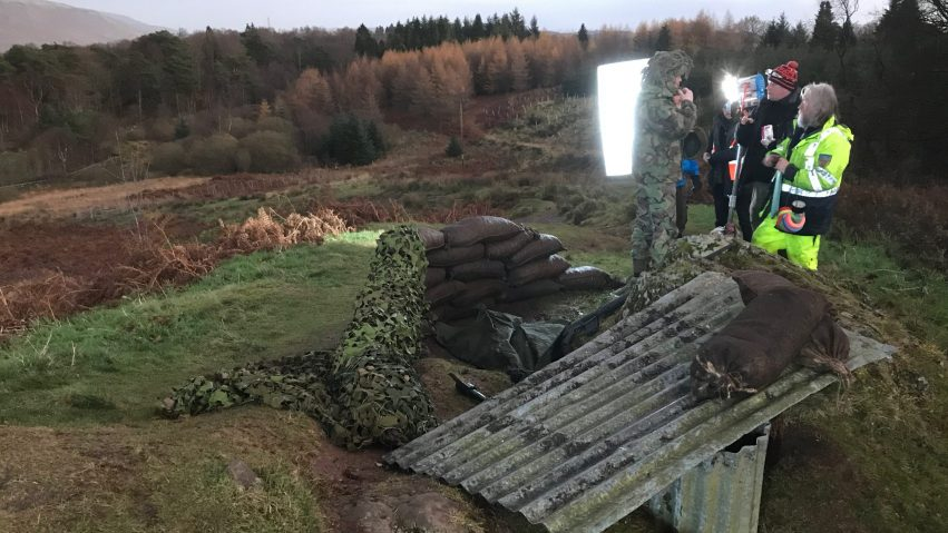 A war set built upon a hill for an Erskine TV Advert shows the cast discussing the scene with the director and crew.