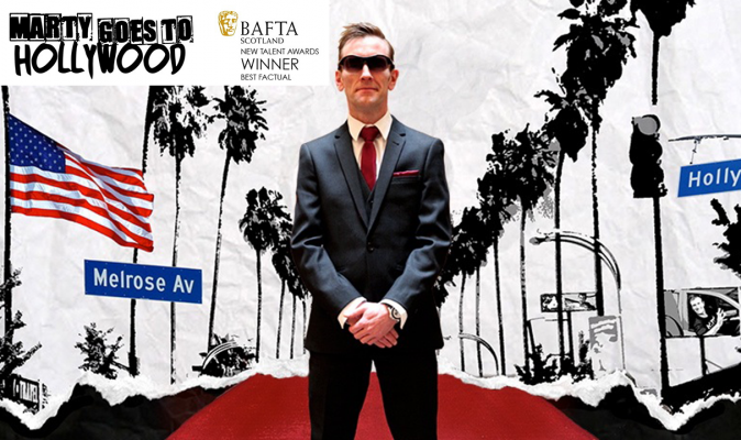 A man stands on a red carpet wearing a suit and sunglasses.