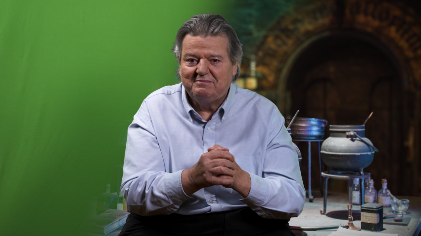 An actor sits in front of a green screen and we can see half of it composited with an old room and lots of science equipment.