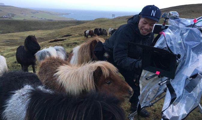 Shetland ponies surround a camera and operator.