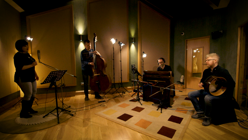 Four musicians recording a track in a music studio.