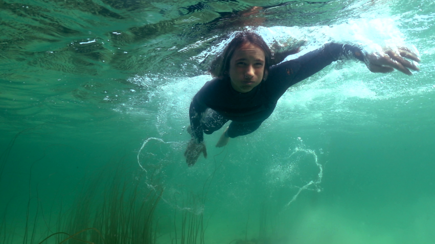 A young boy in a wetsuit swims underwater.