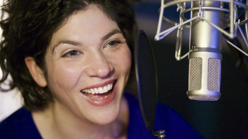 A woman records a VoiceOver into a microphone.